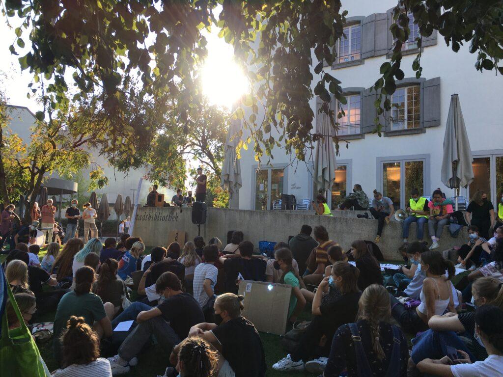 Im Hintergrund ein Gebäude mit einer meterhohen Mauer, die als Bühne dient. Darunter eine Parkwiese. Überall Menschen. Auf der Bühne die Rednerinnen, unten das Publikum. Darüber Sonne und ein Baumast, der ins Bild ragt.